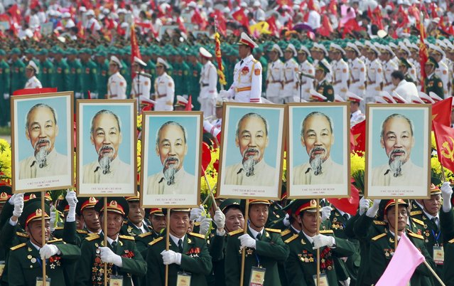 Veterans carry portraits of late Vietnamese revolutionary leader Ho Chi Minh during a parade marking their 70th National Day at Ba Dinh square in Hanoi, Vietnam September 2, 2015. (Photo by Reuters/Kham)