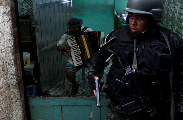 A soldier holds a handgun as a resident plays an accordion during an operation after violent clashes between drug gangs in Rocinha slum in Rio de Janeiro, Brazil, September 22, 2017. (Photo by Ricardo Moraes/Reuters)