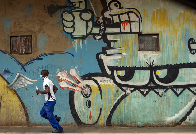 A man wearing face masks to protect against coronavirus, runs past a mural on the street in downtown Johannesburg, South Africa, Thursday, April 9, 2020. South Africa and more than half of Africa's 54 countries have imposed lockdowns, curfews, travel bans or other restrictions to try to contain the spread of COVID-19. (Photo by Themba Hadebe/AP Photo)