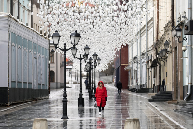 A woman walks through an almost empty pedestrian street in Moscow, Russia, Tuesday, April 14, 2020. Russian President Vladimir Putin has ordered most Russians to stay off work until the end of April as part of a partial economic shutdown to stymie the spread of the coronavirus. (Photo by Alexander Zemlianichenko/AP Photo)