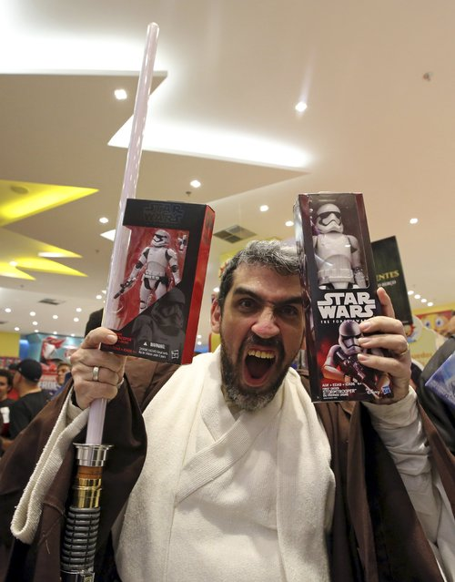 """A man dressed as Obi-Wan Kenobi reacts as he buy new toys from the upcoming film """"Star Wars: The Force Awakens"""" on """"Force Friday"""" in Sao Paulo, Brazil, September 4, 2015. (Photo by Paulo Whitaker/Reuters)"""