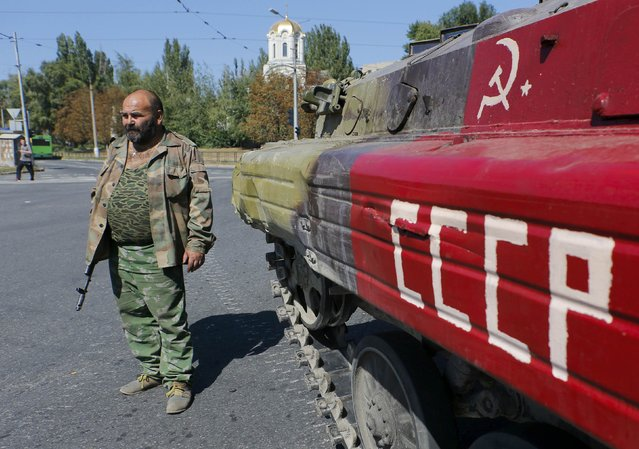 An armed pro-Russian separatist stands next to an APC in the city of Donetsk, eastern Ukraine, September 2, 2014. (Photo by Maxim Shemetov/Reuters)