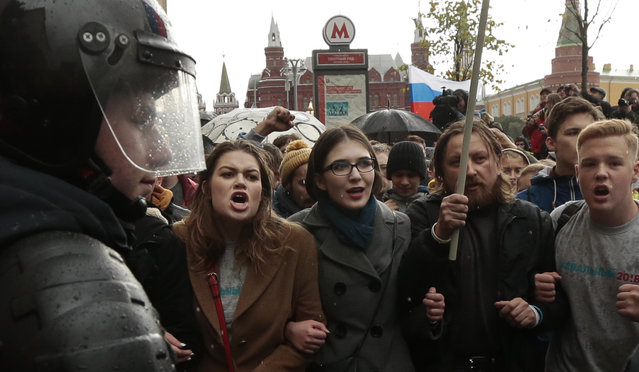 Riot police officers block protesters with Russian flags during a rally in Moscow, Russia, Saturday, October 7, 2017. (Photo by Ivan Sekretarev/AP Photo)