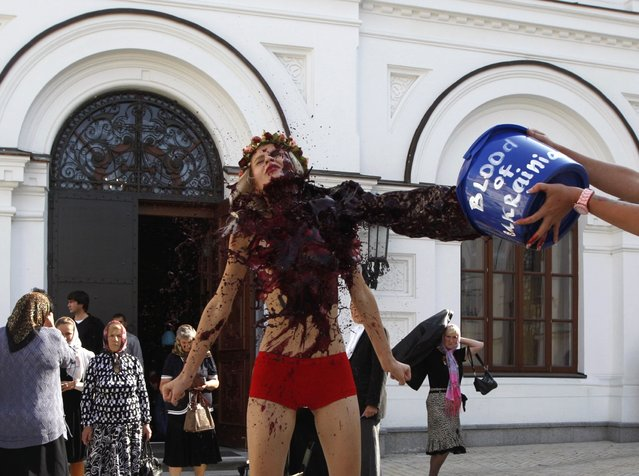 Activists of Ukrainian womens' rights group FEMEN stage a protest at the Kiev Pechersk Lavra monastery in Kiev, September 11, 2014. The group was protesting against the Ukrainian Orthodox Church of the Moscow Patriarchate, which supports Russian agression in Ukraine, the Femen activists said. (Photo by Valentyn Ogirenko/Reuters)