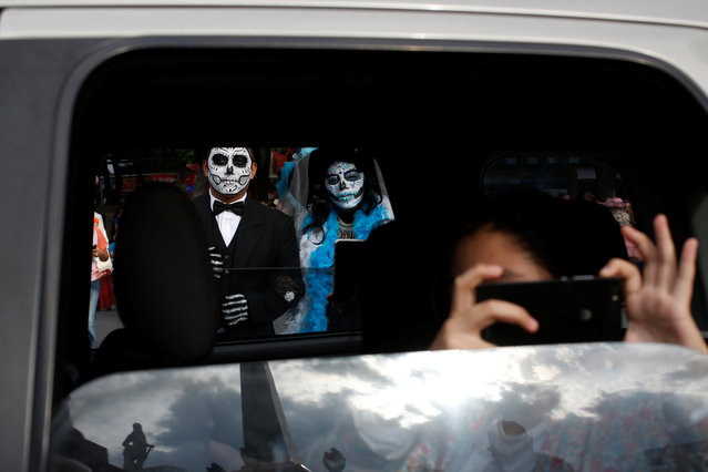 """A woman dressed up as """"Catrina"""", a Mexican character also known as """"The Elegant Death"""", takes part in a Catrinas parade while a woman takes a photograph from inside a vehicle in Mexico City, Mexico on October 22, 2017. (Photo by Carlos Jasso/Reuters)"""
