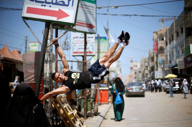 Palestinian man Mohammed al-Hoor, 23, demonstrates his street workout skills in Nuseirat refugee camp, in the central Gaza Strip on May 2, 2017. (Photo by Mohammed Salem/Reuters)