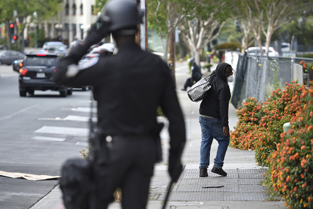 A looter walks away from a police officer in downtown Walnut Creek, Calif., on Sunday, May 31, 2020. (Photo by Jose Carlos Fajardo/Bay Area News Group)