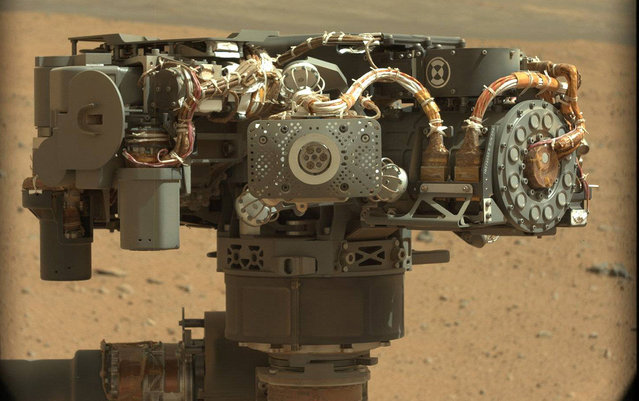 On Mars, NASA's Curiosity rover images itself – this image shows the rover's Alpha Particle X-Ray Spectrometer (APXS), with the Martian landscape in the background. The image was taken by Curiosity's Mast Camera on the 32nd Martian day, or sol, of operations on the surface (September 7, 2012). APXS can be seen in the middle of the picture. This image let researchers know that the APXS instrument had not become caked with dust during Curiosity's dusty landing. Scientists enhanced the color in this version to show the Martian scene as it would appear under the lighting conditions we have on Earth, which helps in analyzing the terrain. (Photo by NASA/JPL-Caltech/MSSS)