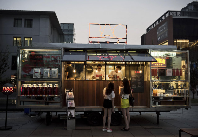 Chinese buy drinks outside a bar in the trendy Sanlitun neighborhood on September 5, 2014 in Beijing, China. The shopping district, known for its high end shops and restaurants is frequented by affluent locals and foreigners. (Photo by Kevin Frayer/Getty Images)