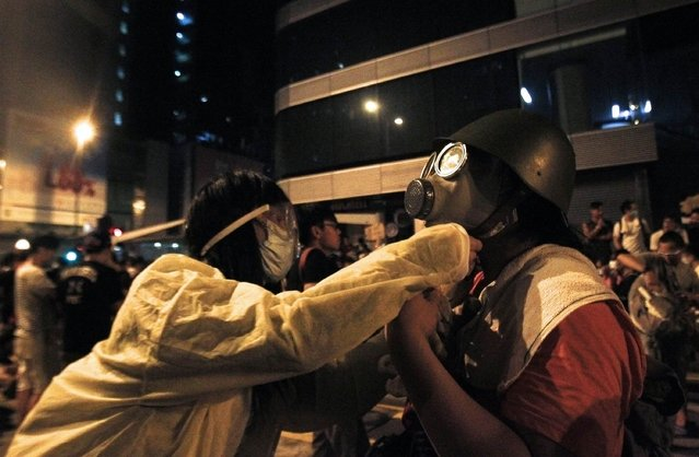 A protester is helped by another to put on a gas mask to prepare for a possible tear gas attack as hundreds of protesters block a main road at Hong Kong's shopping Mongkok district September 29, 2014. (Photo by Liau Chung-ren/Reuters)