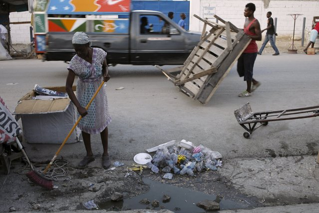 A woman sweeps along a street in Port-au-Prince, Haiti, March 7, 2016. (Photo by Andres Martinez Casares/Reuters)