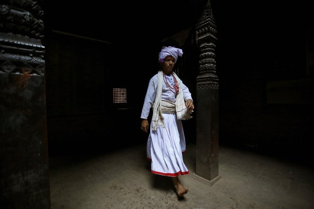 """A priest walks inside a temple while taking part in a sacrificial ceremony of a buffalo during the """"Dashain"""", Hinduism's biggest religious festival in Bhaktapur October 2, 2014. (Photo by Navesh Chitrakar/Reuters)"""