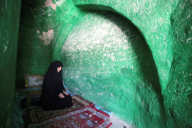 """A woman prays inside the shrine of Imam Mahdi at the Wadi al-Salam cemetery, Arabic for """"Peace Valley"""", in Najaf, south of Baghdad, Iraq, August 1, 2016. (Photo by Alaa Al-Marjani/Reuters)"""