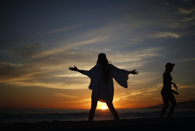 Women watch the sun set over the Pacific Ocean on the beach in Santa Monica, California October 3, 2014. Southern California sizzled in a heat wave as temperatures soared above 100 degrees Fahrenheit in parts of Los Angeles. (Photo by Lucy Nicholson/Reuters)
