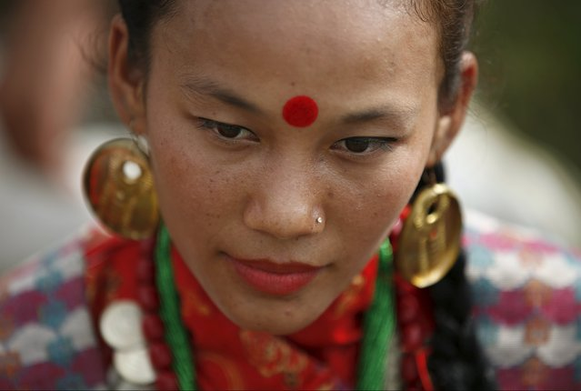 A woman dressed in traditional attire takes part in a celebration a day after the first democratic constitution was announced in Kathmandu, Nepal September 21, 2015. (Photo by Navesh Chitrakar/Reuters)
