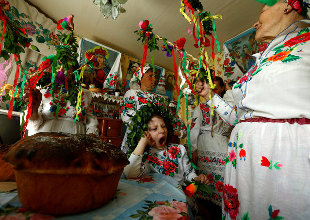 Villagers take part in a ritual celebrating the pagan god Yurya, a time when they don national dress and make offerings out of colourful ribbons and paper in the hope of plentiful harvests in the future. (Photo by Vasily Fedosenko/Reuters)