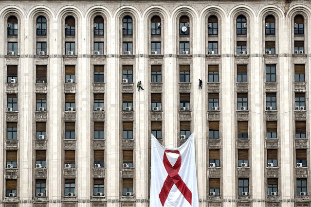 Workers lift a large AIDS awareness banner on the facade of a communist era building – a replica of the Lomonosov Moscow State University – now hosting the offices of some of the leading Romanian newspapers, in Bucharest, November 25, 2012. According to non-governmental organizations, more than 10,000 people live with AIDS in Romania but the actual number could be much higher as testing for the infection is not popular among Romanians. (Photo by Vadim Ghirda/Associated Press)