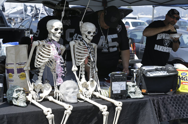 A pair of skeletons sit next to tailgaters before the start of an NFL preseason football game between the Oakland Raiders and the Tennessee Titans Saturday, August 27, 2016, in Oakland, Calif. (Photo by Ben Margot/AP Photo)