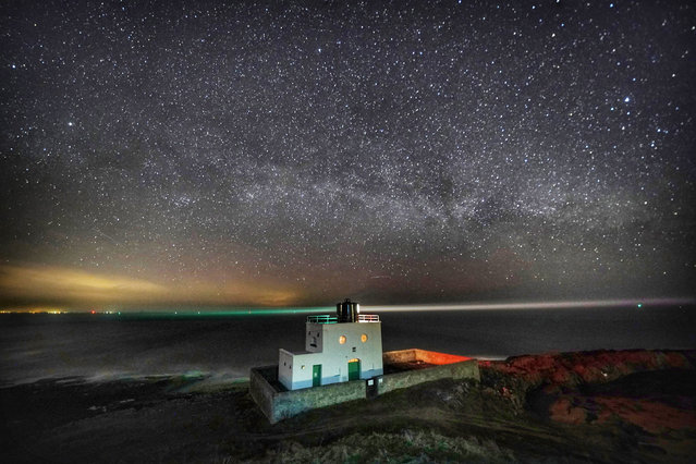 The Milky Way over Bamburgh lighthouse at stag Rock in Northumberland, England on March 23, 2020. (Photo by Owen Humphreys/PA Images via Getty Images)