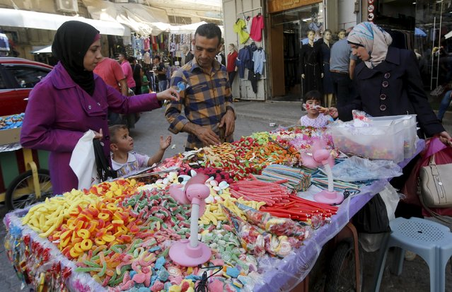 Palestinian customers buy candies from a vendor at a shop in the old market ahead of the Eid al-Adha festival, in the West Bank city of Nablus September 23, 2015. Muslims across the world are preparing to celebrate the annual festival of Eid al-Adha or the Feast of the Sacrifice, which marks the end of the annual haj pilgrimage. (Photo by Abed Omar Qusini/Reuters)