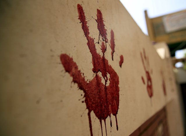 A bloodied handprint from the blood of a freshly slaughtered calf is seen on the wall on the first day of Eid al-Adha festival in Toukh, El-Kalubia governorate, northeast of Cairo, Egypt, September 24, 2015. (Photo by Amr Abdallah Dalsh/Reuters)