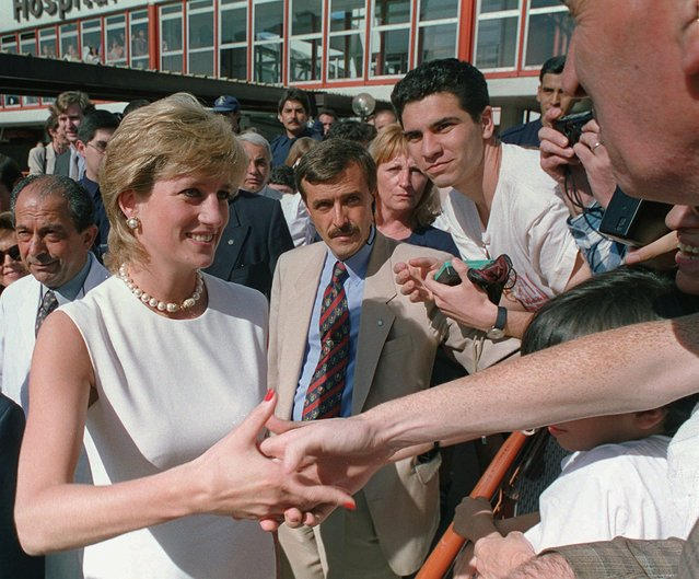 Princess Diana shake hands with well-wishers as she leaves the Children's Hospital in downtown Buenos Aires, Thursday, November 23, 1995, during the first day of her four-day visit to Argentina. Escaping the furor over her public confession of adultery, Princess Diana arrived in Argentina on Thursday, seeking to boost her profile as a roving ambassador. (Photo by Daniel Muzio/AP Photo)