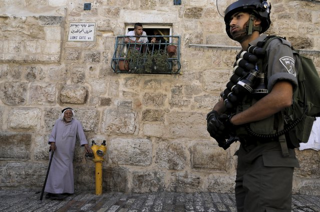 A Palestinian man looks on from a window as an Israeli border police officer (R) stands guard near the Lions Gate in the Old City of Jerusalem September 28, 2015. (Photo by Ammar Awad/Reuters)