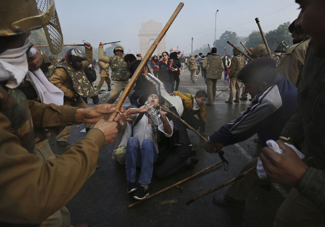 Protesters shield themselves as Indian police beat them with sticks during a violent demonstration near the India Gate in New Delhi, on December 23, 2012. (Photo by Kevin Frayer/AP Photo)