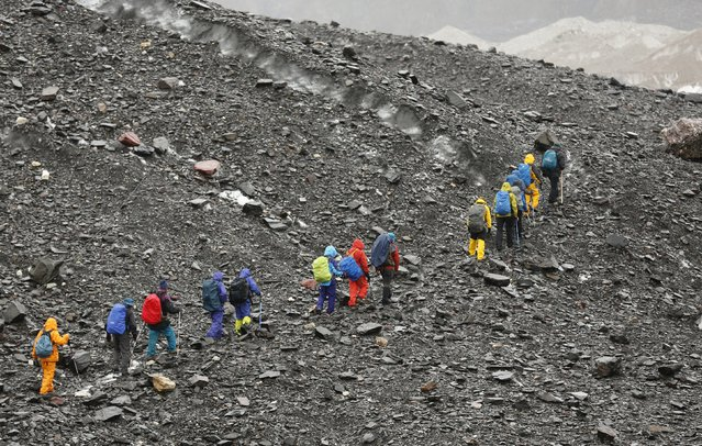 A group of Japanese trekkers climbs the rock-covered Baltoro glacier in the Karakoram mountain range in Pakistan September 3, 2014. (Photo by Wolfgang Rattay/Reuters)