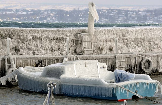 An ice-covered boat sits at a landing stage at the Lake of Geneva in Versoix, Switzerland on February 3, 2012. (Photo by Martial Trezzini/Keystone)