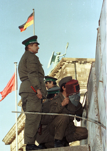 Border guards repair a section of the Berlin Wall, after protesters knocked it over earlier during the day, November 11, 1989. (Photo by Reuters)