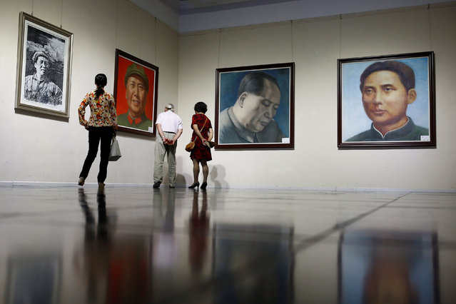 People look at portraits of late Chinese Chairman Mao Zedong during the opening of an exhibition of Mao related art in Beijing, China, September 8, 2016. (Photo by Thomas Peter/Reuters)
