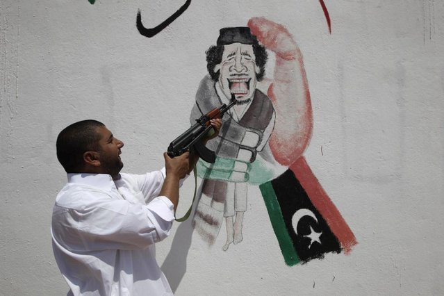 A rebel fighter points his weapon at graffiti of Muammar Gaddafi on a checkpoint building controlled by rebels in Zintan July 15, 2011. (Photo by Ammar Awad/Reuters)