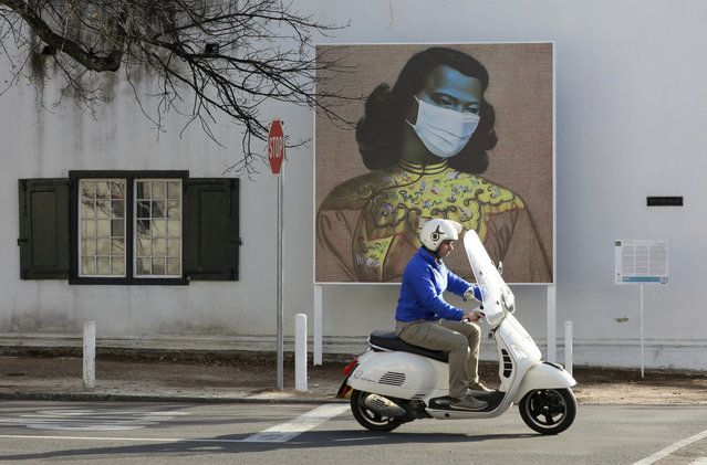 "A man rides his scooter in front of a marked version of Vladimir Tretchikoff's ""The Chinese Girl, The Green Lady"" painting in Stellenbosch, South Africa, Thursday August 13, 2020. The public art is part of a series called Masked Masterpieces of masks superimposed on famous South African artworks to support Stellenbosch University students impacted by Covid-19. (Photo by Nardus Engelbrecht/AP Photo)"