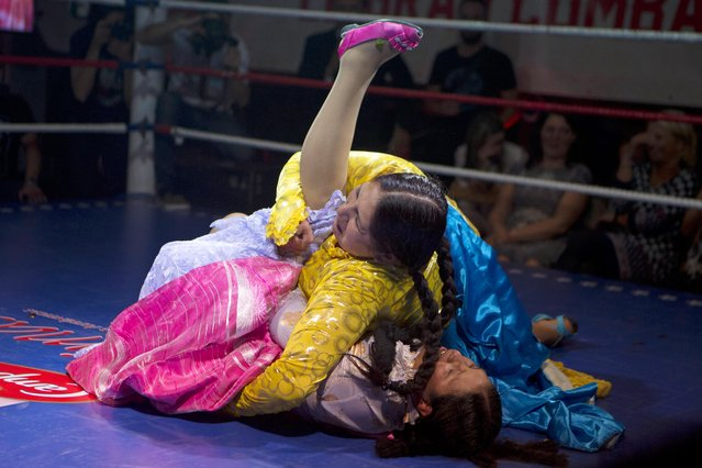 "Yenny Mamani ""Marta la Altena"", top, grabs Leonor Cordova ""Angela la Simpatica"" in a hold during a Bolivian wrestling Cholitas fight in Madrid, Spain, Thursday October 8, 2015. (Photo by Paul White/AP Photo)"