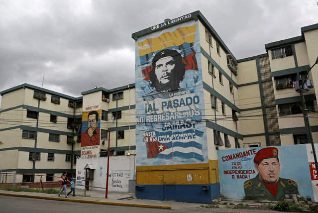 "People walk past murals of Venezuela's late president Hugo Chavez and Argentine revolutionary hero Ernesto ""Che"" Guevara (C) in Caracas, Venezuela September 8, 2016. (Photo by Henry Romero/Reuters)"