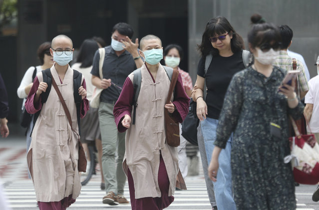 People wear face masks to protect against the spread of the coronavirus as they walk in downtown Taipei, Taiwan, Thursday, September 10, 2020. (Photo by Chiang Ying-ying/AP Photo)