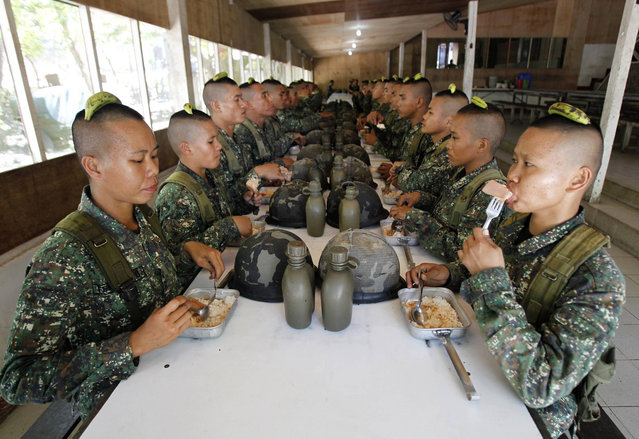 Newly recruited female marines take their lunch with fellow soldiers after undergoing drills inside the marine headquarters in the town of Ternate, Cavite city, south of Manila,  on February 6, 2013. There are an estimated 350 women combatants in the 10,000-member Philippine marines who go through the same rigid physical and mental training as their men counterparts. Since 2006, female marine officers of the Marine Corps have been performing in the field of assault armor, field artillery, airborne and other combat duties, a marine officer said. (Photo by Romeo Ranoco/Reuters)