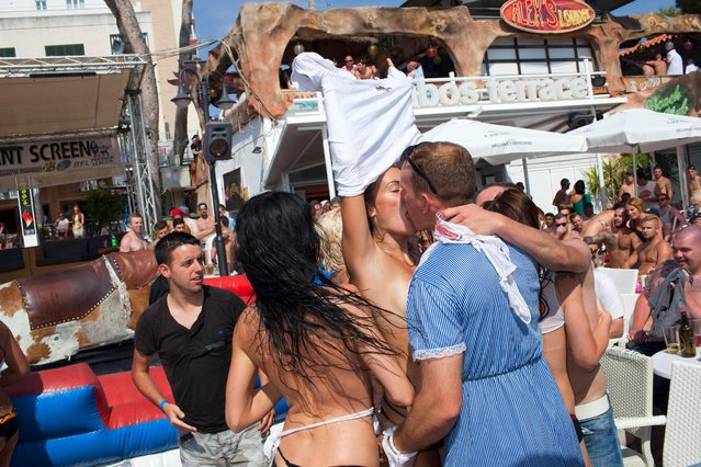 Rob, a British man in his late 20's in Magaluf, Majorca on his stag party, kisses a participant in a wet t-shirt competition hosted at Mambo's Terrace on June 28, 2013. (Photo by Peter Dench/Getty Images Reportage)