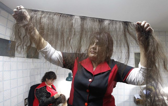 Workers Edith Marfil (L) and Marcela Reyes (C) make natural hair wigs to be donated to girls undergoing chemotherapy for cancer, at the workshop owned by hair stylist Marcelo Avatte in Santiago, August 22, 2014. (Photo by Rodrigo Garrido/Reuters)