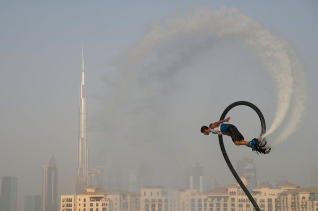 A man rides a flyboard with the Burj Khalifa, the world's tallest building, in the distance in Dubai, United Arab Emirates, Thursday, June 25, 2020. Dubai has begun to allow sporting events again amid the coronavirus pandemic and the Dubai International Marine Club hosted a water sports event Thursday to celebrate. (Photo by Jon Gambrell/AP Photo)