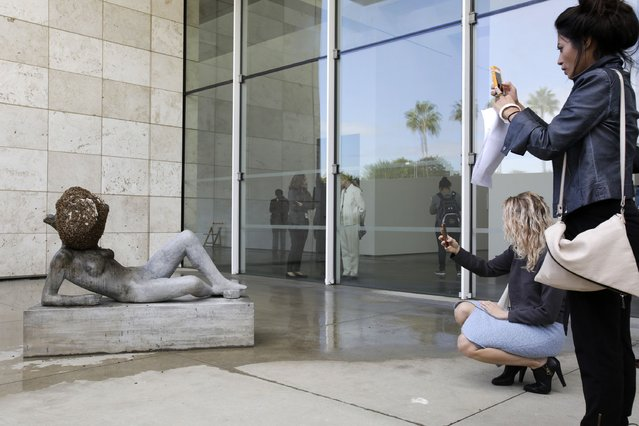 """Visitors photograph """"Untilled (Liegender Frauenakt)"""", a concrete figure with a wax beehive and live bees, during a press preview of French artist Pierre Huyghe's first major retrospective at the Los Angeles County Museum of Art (LACMA) in Los Angeles, California November 19, 2014. (Photo by Jason Redmond/Reuters)"""