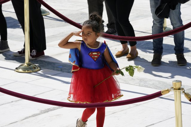 A child in a Supergirl costume pays respects as Justice Ruth Bader Ginsburg lies in repose under the Portico at the top of the front steps of the U.S. Supreme Court building, in Washington, U.S. September 23, 2020. (Photo by Alex Brandon/Pool via Reuters)