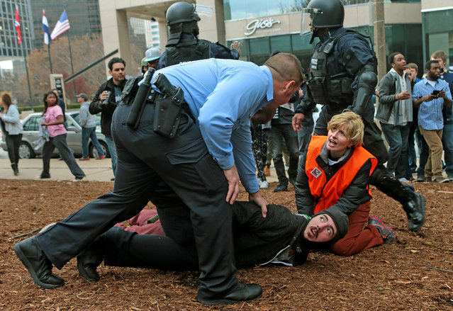 A clergy member assists a protester as he is taken to the ground on Sunday, November 30, 2014, at Kiener Plaza. Protesters and police clashed following an NFL football game between the St. Louis Rams and the Oakland Raiders as protests continued following a grand jury's decision not to indict a Ferguson police officer in the shooting death of Michael Brown. (Photo by Laurie Skrivan/AP Photo/St. Louis Post-Dispatch)