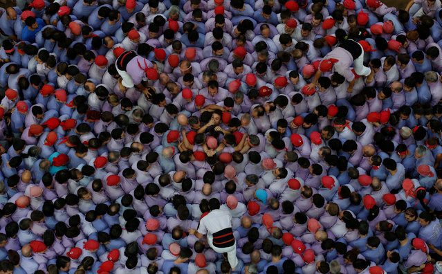 """Colla Jove Xiquets de Tarragona start to form a human tower called """"castell"""" during a biannual competition in Tarragona city, Spain, October 2, 2016. (Photo by Albert Gea/Reuters)"""
