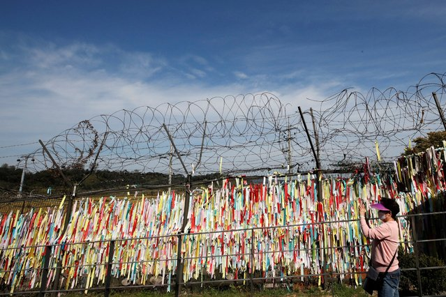 """A woman wearing a face mask holds her smartphone near the wire fences decorated with ribbons written with messages wishing for the reunification of the two Koreas at the Imjingak Pavilion in Paju, South Korea, Sunday, October 11, 2020. North Korean leader Kim Jong Un warned that his country would """"fully mobilize"""" its nuclear force if threatened as he took center stage at a military parade that unveiled what appeared to be a new intercontinental ballistic missile and other weapons Saturday. (Photo by Lee Jin-man/AP Photo)"""