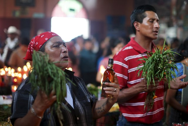 Men pray in the church in honor of San Simon in Iztapa, Chimaltenango, Guatemala, October 28, 2015. (Photo by Jorge Dan Lopez/Reuters)