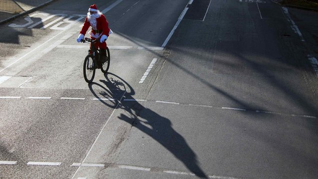A man dressed as Father Christmas rides a bicycle during the Nikolaus Lauf (Santa Claus Run) in the east German town of Michendorf, southwest of Berlin December 7, 2014. (Photo by Hannibal Hanschke/Reuters)