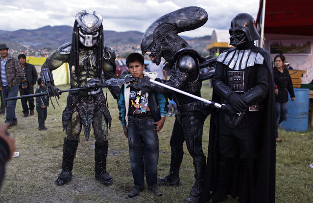 A boy poses for a picture with people wearing costumes of famous sci-fi movies during the Canaan fair which is part of the Holy Week celebrations in Ayacucho, Peru, on March 28, 2013. (Photo by Rodrigo Abd/AP Photo /The Atlantic)