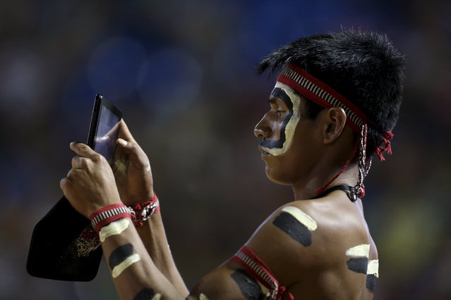 An indigenous man from the Bororo tribe take a picture during the closing ceremony of the first World Games for Indigenous Peoples in Palmas, Brazil, October 31, 2015. (Photo by Ueslei Marcelino/Reuters)